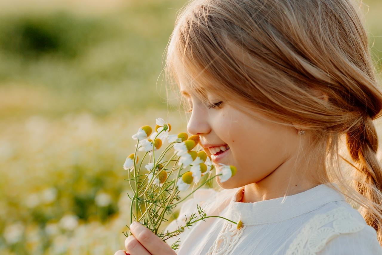 closeup-portrait-little-girl-sniffing-daisies
